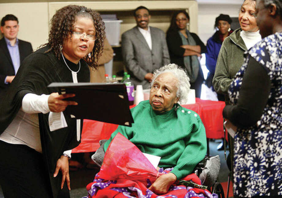 Hour photos / Erik TrautmannAssistant Library Director Sherelle Harris honors Marguerite Fuller with a certificate as the South Norwalk Branch Library celebrates Black History Month by honoring five local African-American men and women, including Fuller, Saturday afternoon. / (C)2012, The Hour Newspapers, all rights reserved