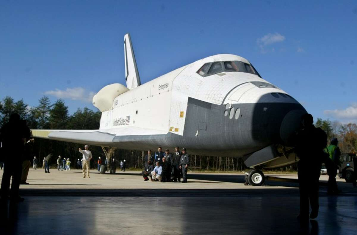 FILE- In this Nov. 20, 2003 file photo, workers pose in front of the Space Shuttle Enterprise prior to moving it into the new Steven F. Udvar-Hazy Center at Dulles Airport in Chantilly, Va. Enterprise is scheduled to arrive in New York on the back of a NASA jumbo jet on Friday, April 27, 2012, where it will be stored in an hangar at John F. Kennedy International Airport before assuming its new permanent location on the deck of the Intrepid Air and Space Museum in New York Harbor. (AP Photo/Lisa Nipp, File)