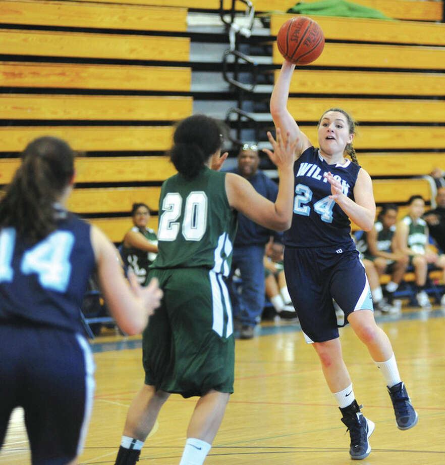Hour photo/John NashWilton's Casey Pearsall, right, looks to dump a pass into the low post to senior classmate Alyssa Malvarosa during Friday's regular-season finale against Bassick. The Warriors won the game, 44-28, to clinch the top-seed for the FCIAC playoffs.