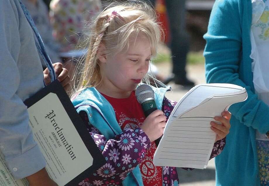 Hour Photo/ Alex von Kleydorff. Naramake Kindergartner Olivia Romero reads a poem she wrote about trees during Arbor Day at the school