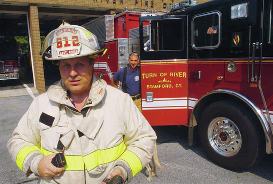 From left, Matthew Maounis, assistant chief of the Turn of River Volunteer Fire Deptartment, and firefighter Frank Maduri at the department's Turn of River Road headquarters. Hour photo / Erik Trautmann / (C)2011, The Hour Newspapers, all rights reserved