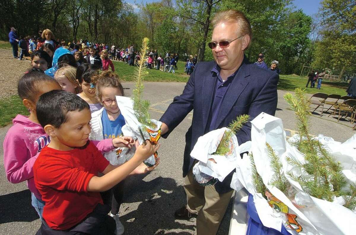 Hour Photo/ Alex von Kleydorff. Doug Pistawka with CL&P passes out evergreen seedlings to all the students after Arbor Day ceremony at Naramake School
