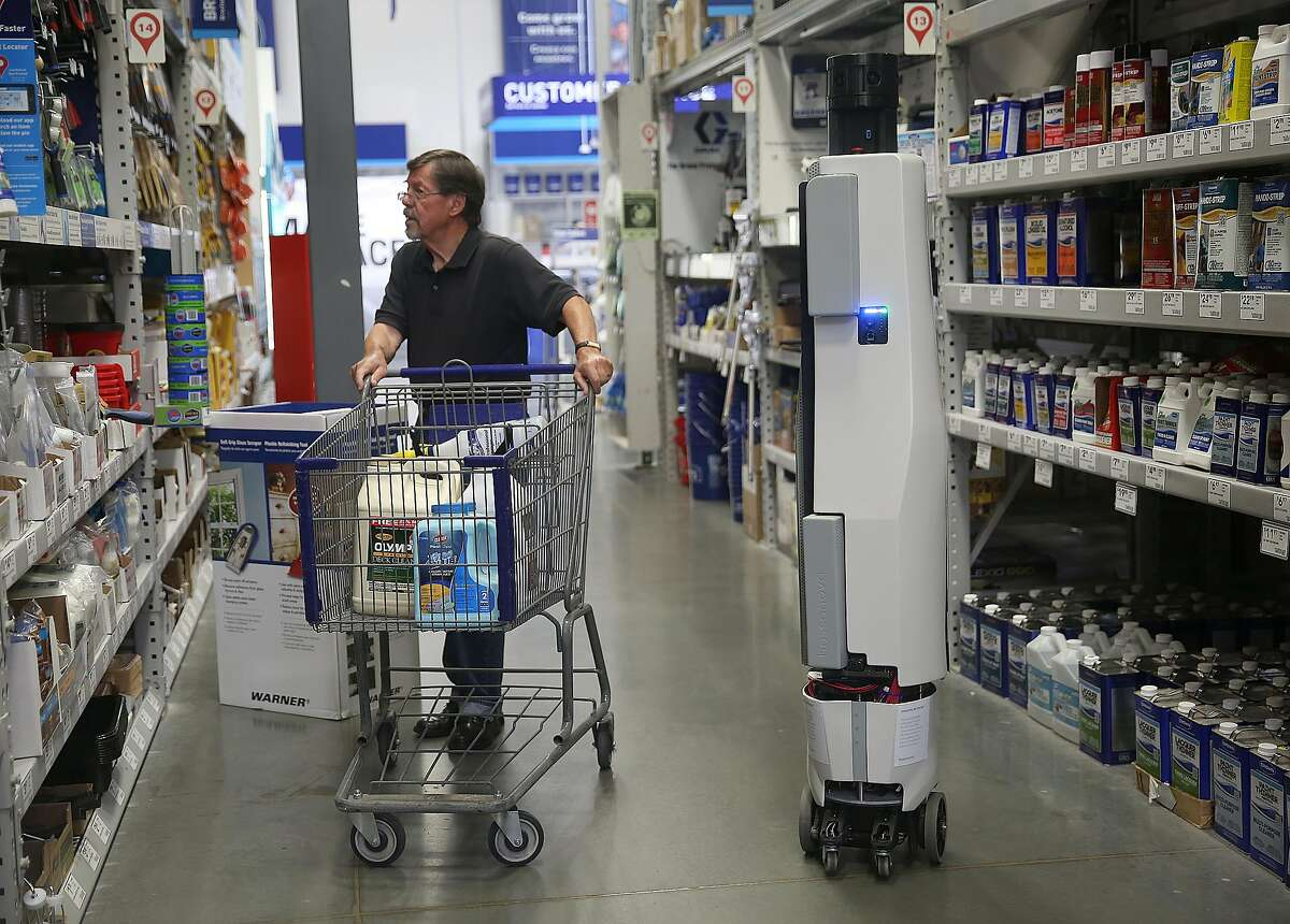 Customer Larry Ludgus (left) looks for products to refurbish teak deck furniture as a Bossa Nova Robot passes him down an aisle at Lowe's on Tuesday, June 14, 2016 in Sunnyvale, Calif.