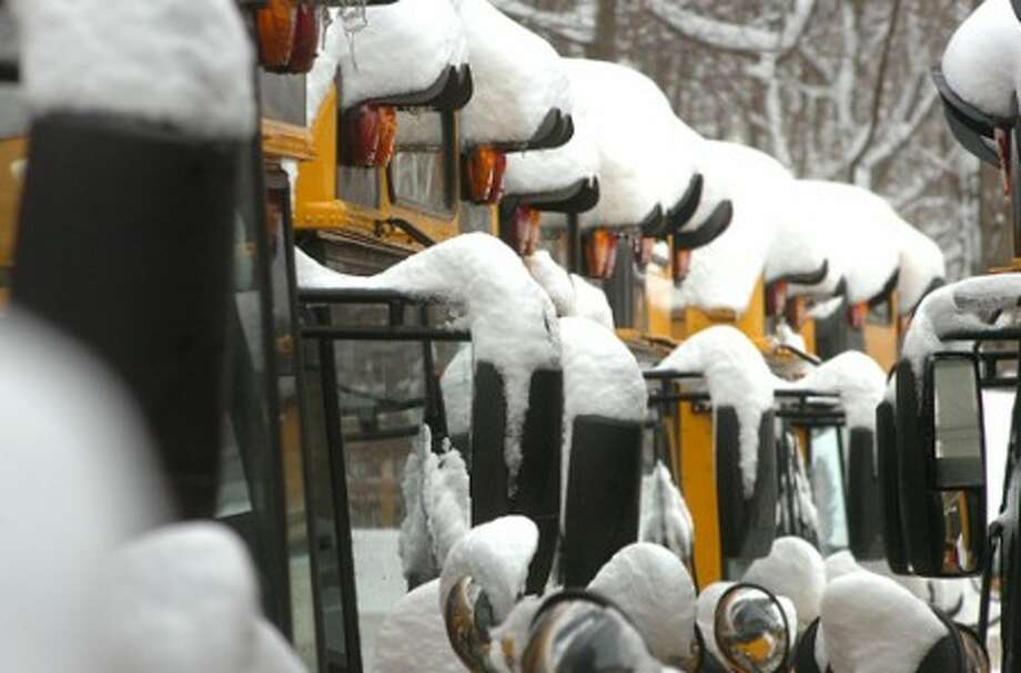 Photo/Alex von Kleydorff. School Buses sit at the Bus barn covered with snow in Wilton on Thursday another day of school cancelled due to snow.
