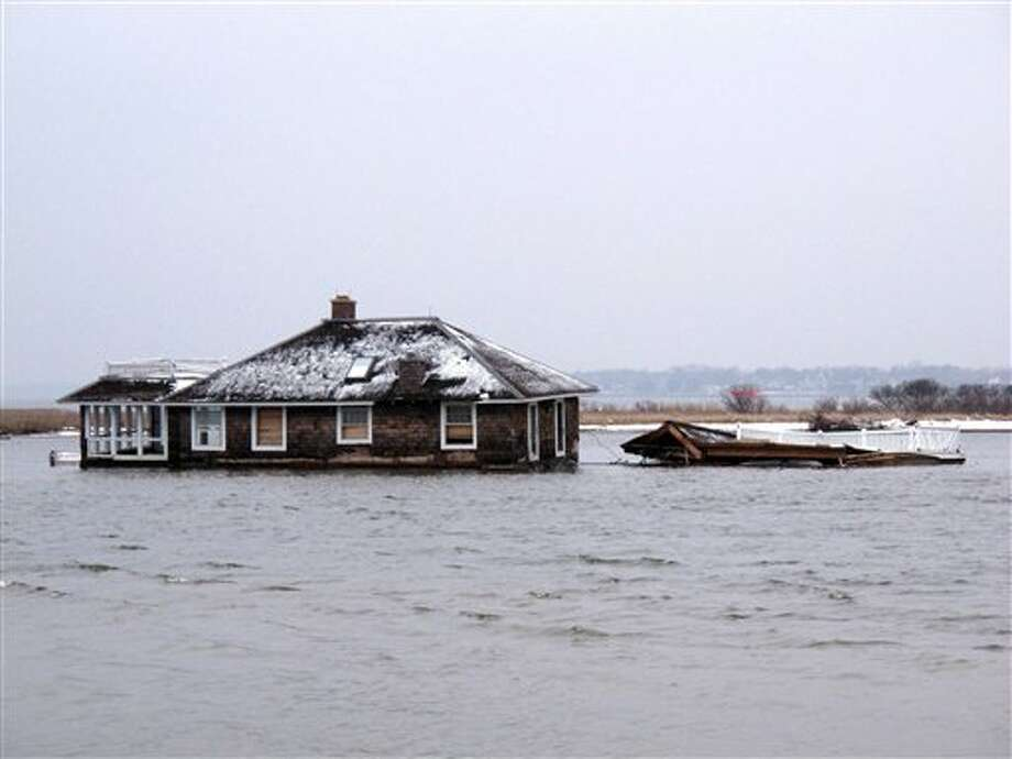 This Feb. 5, 2013, photo,shows a home in the middle of Barnegat Bay, that was washed into the Bay from Mantoloking N.J. during Superstorm Sandy. States hit hard by Sandy are gearing up to remove tons of debris from waterways, including houses, vehicles, sunken boats, furniture, pieces of piers, decks and bulkheads _ all of which must be removed before the summer swimming and boating season. (AP Photo/Wayne Parry) / AP