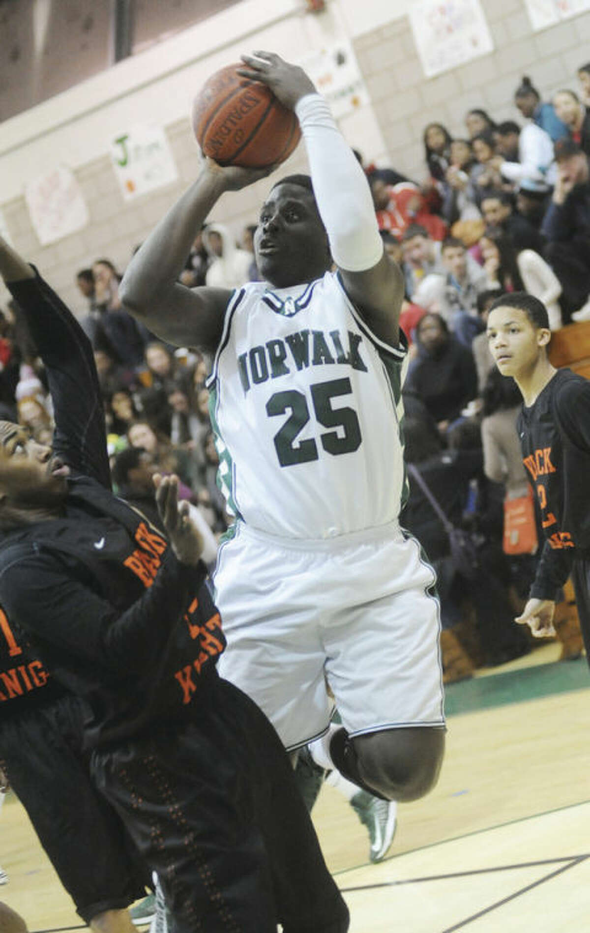 Hour photo/Matthew Vinci Norwalk's Saeed Soulemane (25) goes up for a shot over Tamarie Sterling of Stamford during Monday night's game at NHS's Scarso Gym. Soulemane had 16 points and 11 rebounds as the Bears turned back the visiting Black Knights, 82-69.