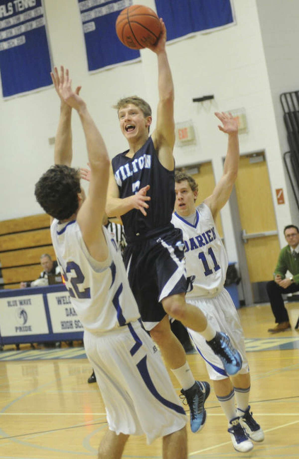 Hour photo/Matthew Vinci An airborne Max Maudsley of Wilton looks to pass over Henry Baldwin of Darien, left, during Monday's game.