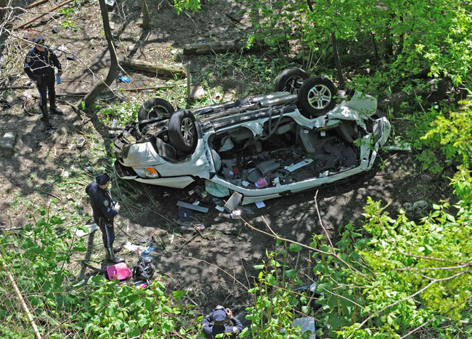 Police investigate the destroyed van that plunged over the Bronx River Parkway, Sunday April 29, 2012, in New York. Authorities say the out-of-control van plunged off a roadway near the Bronx Zoo, killing seven people, including three children. (AP Photo/ Louis Lanzano) / FR77522 AP