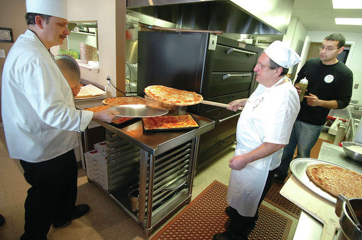 Hour Photo/ Alex von Kleydorff Mario Sforza takes a freshly made pizza out of the oven for Dino at Dino's Pizza Pie in Norwalk.