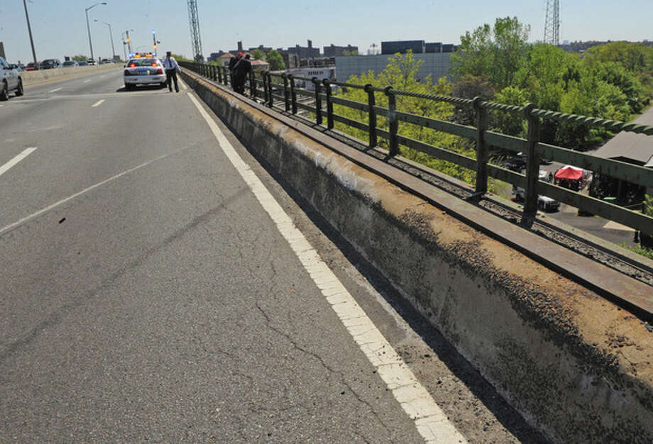 Skid marks and a scraped concrete barrier mark the spot where a van carrying seven occupants plunged off the highway to a wooded area below, Sunday April 29, 2012, in New York. Authorities say the out-of-control van plunged off a roadway near the Bronx Zoo, killing seven people, including three children. (AP Photo/ Louis Lanzano) / FR77522 AP