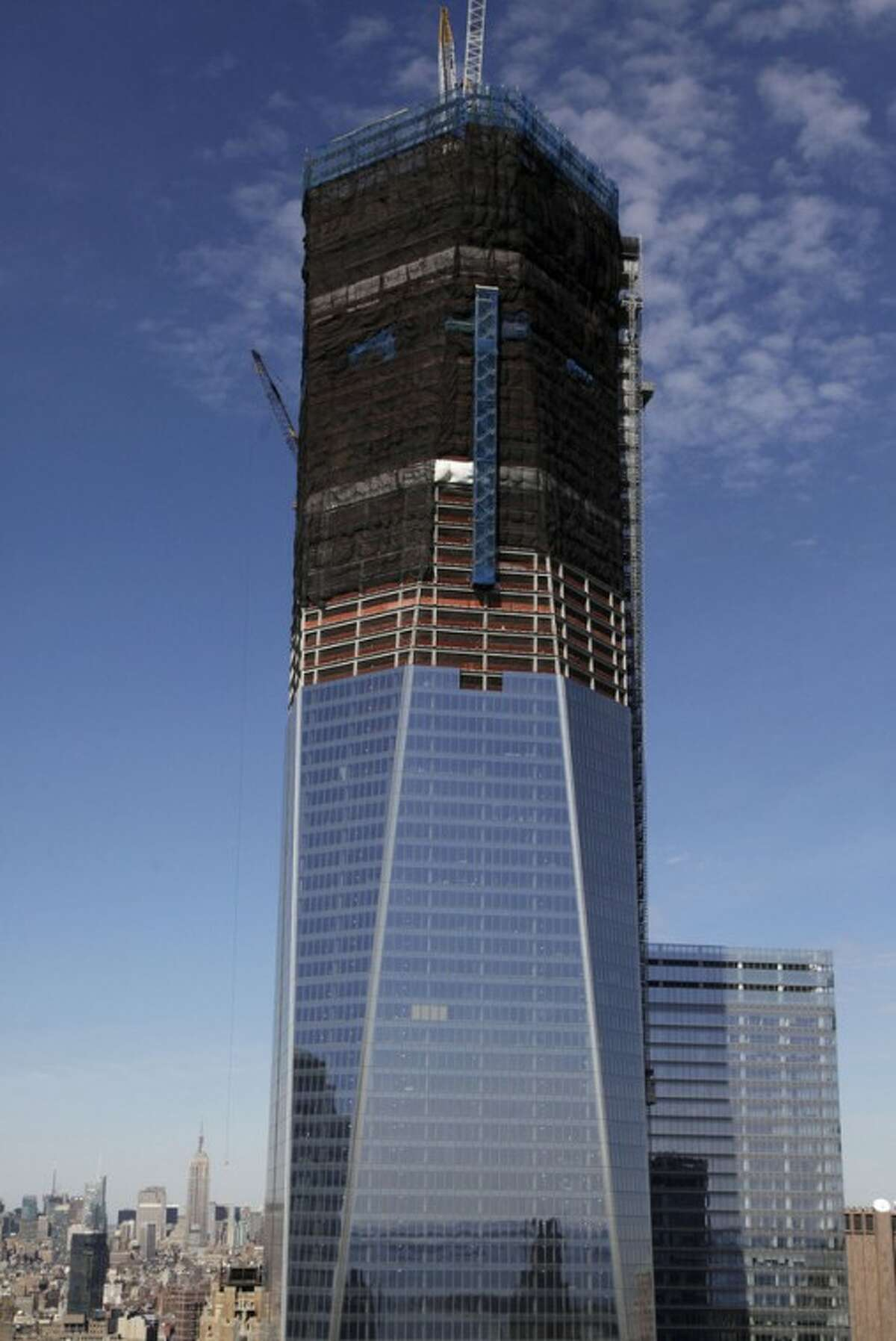 FILE- In this April 17, 2012, file photo, One World Trade Center, now up to 100 floors, rises above the Manhattan skyline in New York. On Monday, April 30, One World Trade Center _ being built to replace the twin towers destroyed on 9/11 _ gets steel columns to make its unfinished framework a little higher than the Empire State Building's observation deck, to become the tallest building in New York. (AP Photo/Mark Lennihan)