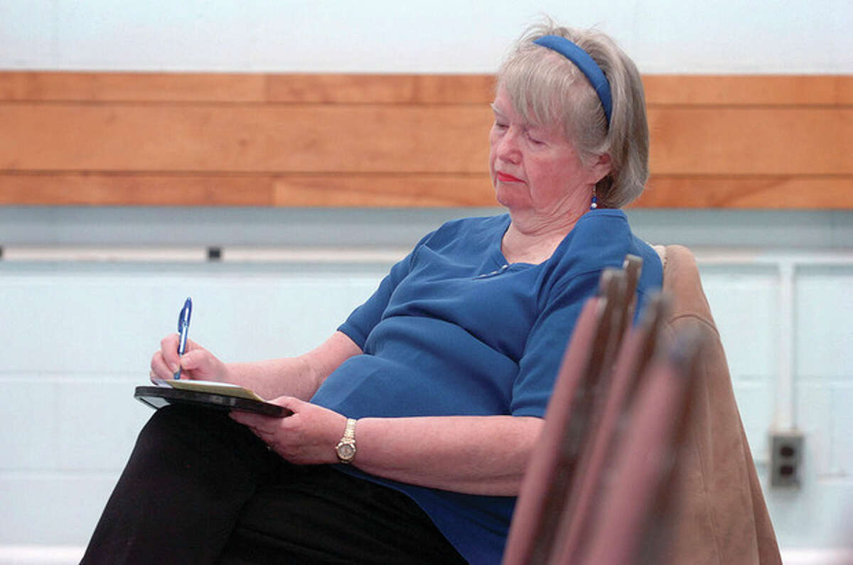 Hour Photo/ Alex von Kleydorff. Anne Richards takes notes during a panel discussion about scams aimed at seniors at The Norwalk Senior Center.