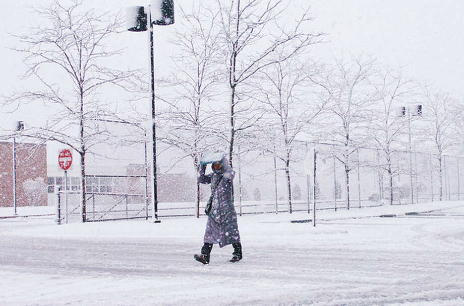 Westport resident Bokyung Choi traverses the frozen parking lot at Bedford Middel School Saturday. Hour photo / Erik Trautmann / (C)2011, The Hour Newspapers, all rights reserved