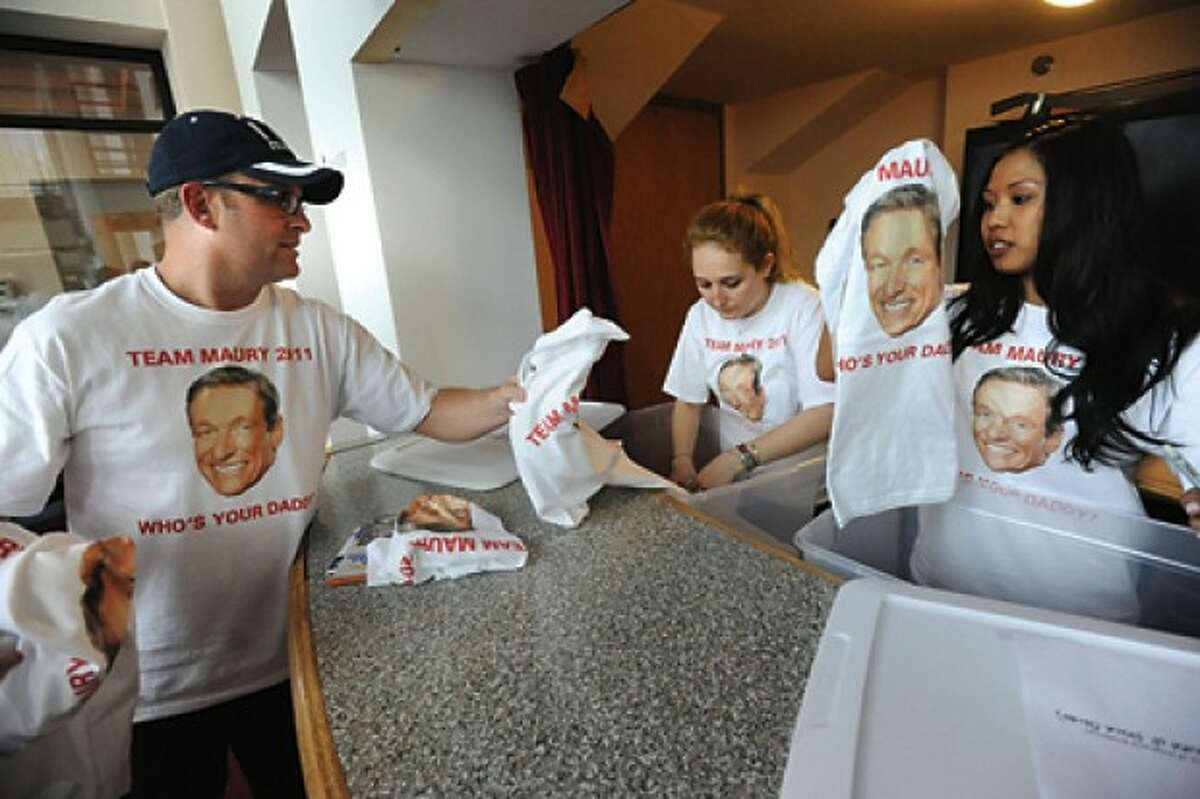 Paul Faulhaber, executive producer of the Maury Povich show gets Team Maury shirts ready for employees to wear for the Stamford Boys and Girls Club 5K race on Thursday. From left is Volunteer Jessica Bloom and Team Maury co-captain Michelle Baetiong. hour phoot/matthew vinci