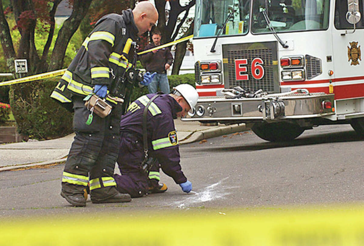 Norwalk Hazardous Material Team members test a strange white substance that was thrown form a car Tuesday afternoon on Couch St.