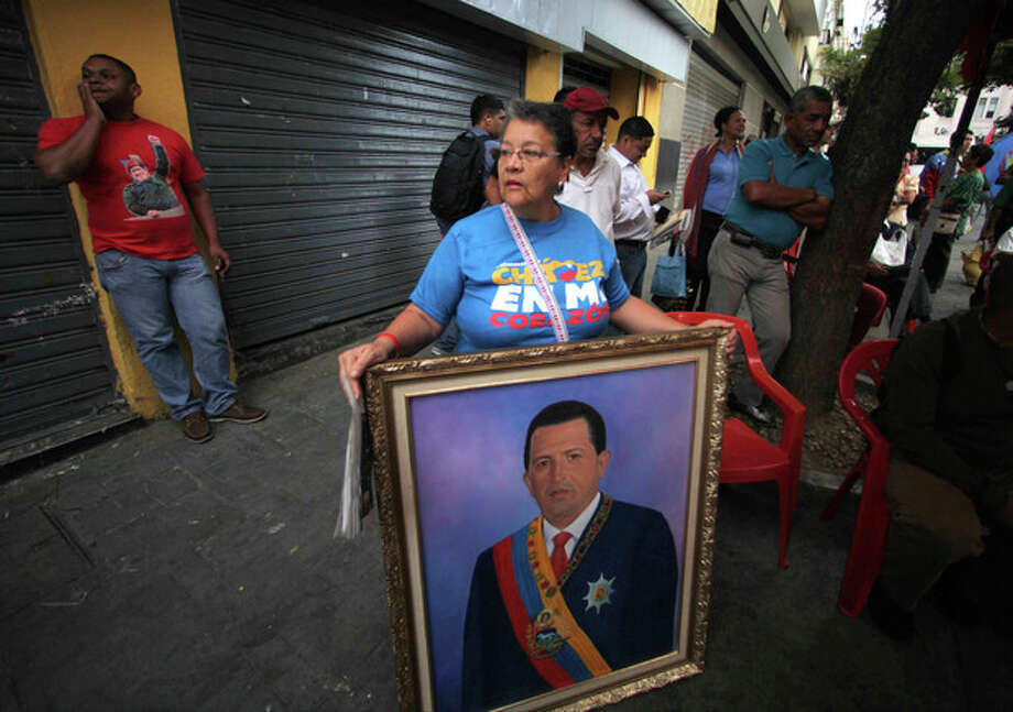 A woman holds a painting of President Hugo Chavez as supporters gather around Bolivar square after his return to the country in Caracas, Venezuela, Monday, Feb. 18, 2013. Chavez returned to Venezuela early Monday after more than two months of medical treatment in Cuba following cancer surgery. The government didn't offer an explanation as to why Chavez made his surprise return while he is undergoing other treatments that have not been specified.(AP Photo/Fernando Llano) / AP