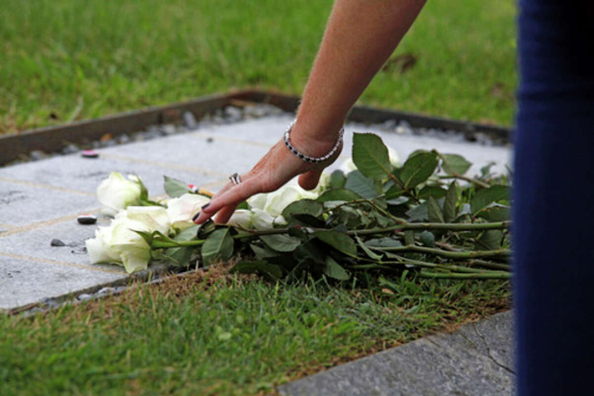 A woman places flowers on her husband's memorial stone during the Connecticut Remembers Steptember 11th Memorial Service held at Sherwood Island State Park Thursday evening.
