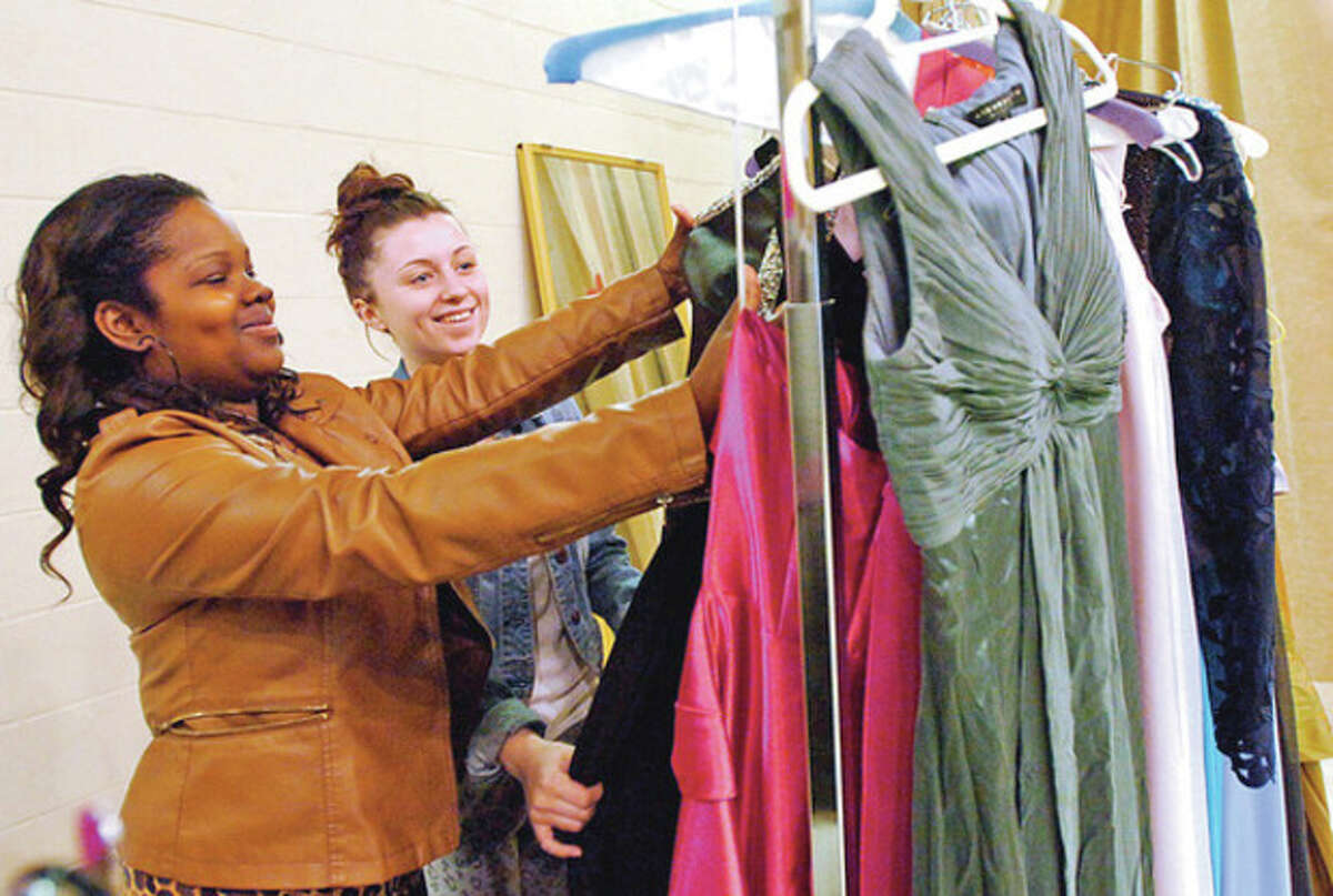 Westhill High School seniors Kimberly Thompson and Katie Dicine look a dresses during the high school's annual prom gown sale Friday. Hour photo / Erik Trautmann