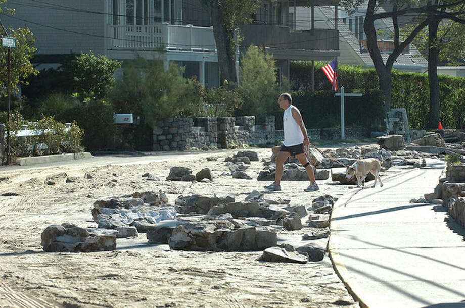 Hour Photo/ Alex von Kleydorff. A man takes a look around and walks his dog along South Beach in Rowayton where the beach and the sea wall were pushed onto the street in Rowayton. / 2011 The Hour Newspapers