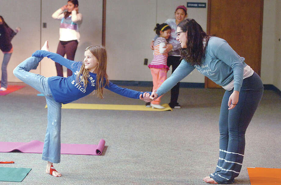 Hour Photo/ Alex von KleydorffInstructor Marianne Erena holds on to 8-year-old Christina Cormier as they work on a Dancers pose during Yoga class at the Norwalk library. / 2013 The Hour Newspapers