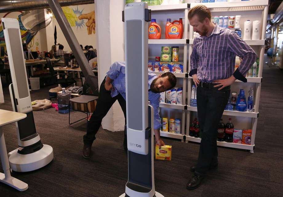 Jeff Gee (left) and Brad Bogolea, Simbe co-founders, show how their Tally robot avoids objects when taking inventory in stores. Photo: Leah Millis, The Chronicle