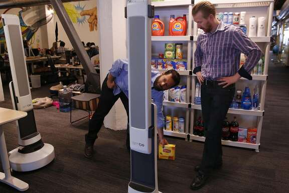 Jeff Gee, Chief of Design and Co-Founder of Simbe, left, and Brad Bogolea, CEO & Founder place a box in front of their shelf-auditing robot Tally as it rolls around to show that it will not run into the object during a demonstration at Simbe's office space June 10, 2016 in San Francisco, Calif.