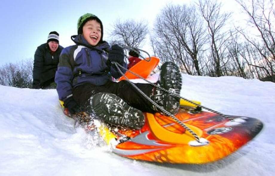 Photo/Alex von Kleydorff. 7yr old Max Jones gets a push from mom Eliza while sledding on Friday in Georgetown.