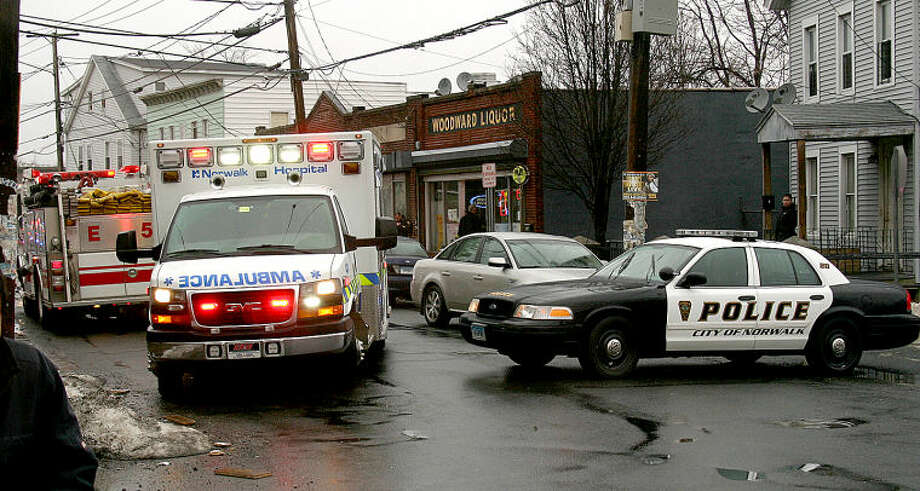 Hour photo / Chris Bosak An ambulance with a shooting victim pulls away from the scene on Woodward Avenue on Saturday.