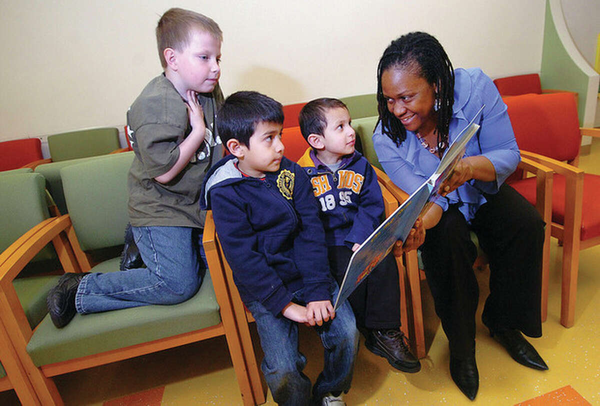 Hour Photo/ Alex von Kleydorff. Eva Beau, Community Outreach Coordinator with the Norwalk Community Health Center reads to young patients in the waiting room of the Pediatric center