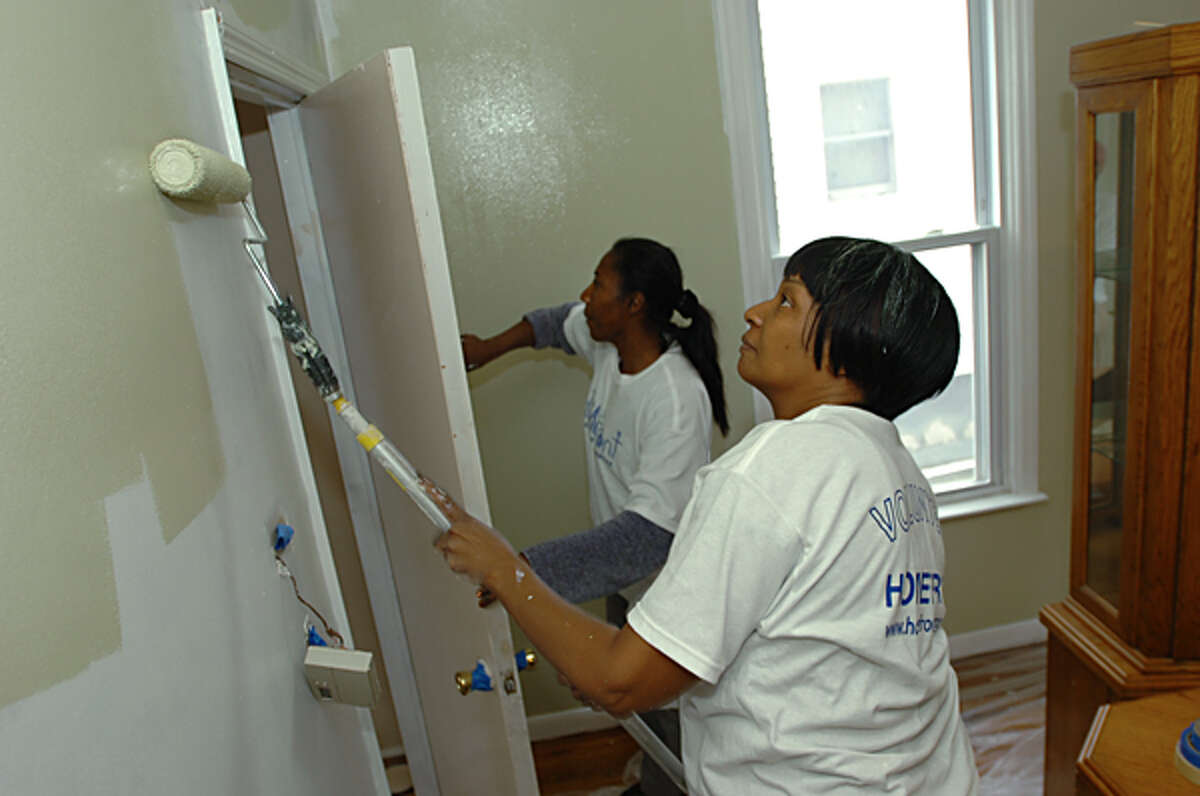 Aletta Tarry volunteers at the home of Diana Maurice, right, helping with renovations as part of the Homefront project organized by Temple Shalom. More than 4,000 volunteers from 84 community groups in Norwalk are observing a local tradition on Saturday by revitalizing 68 homes and eight community centers in need. Hour photo / Erik Trautmann