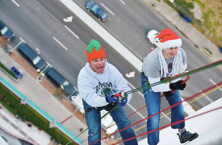 Sports great Bobby Valentine and New York Yankees General manager Brian Cashman rappel from Stamford's 1 Landmark Square building Friday in preparation for Sunday nights Christmas tree lighting.Hour photo / Erik Trautmann / (C)2012, The Hour Newspapers, all rights reserved
