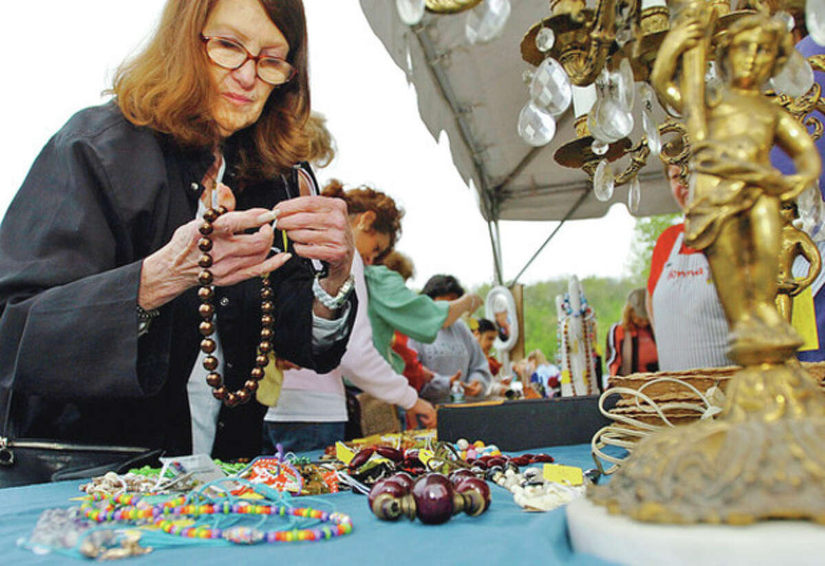 Marilyn Hey looks over some jewelery during the semi-annual Minks to Sinks Spring 2012 rummage sale Saturday that benefits FCA (Family & Children's Agency) of Norwalk. Hour photo / Erik Trautmann