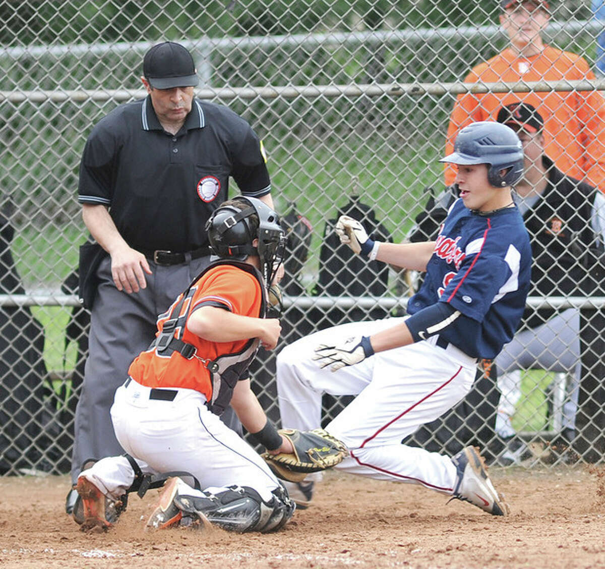 Hour photo/John Nash Brien McMahon's Mike Giordano, right, slides into home as Ridgefield catcher Eric Jones makes the tag in front of the the umpire during Saturday's game in Norwalk. McMahon had three runners thrown out at the plate, but went on to a 3-0 win.