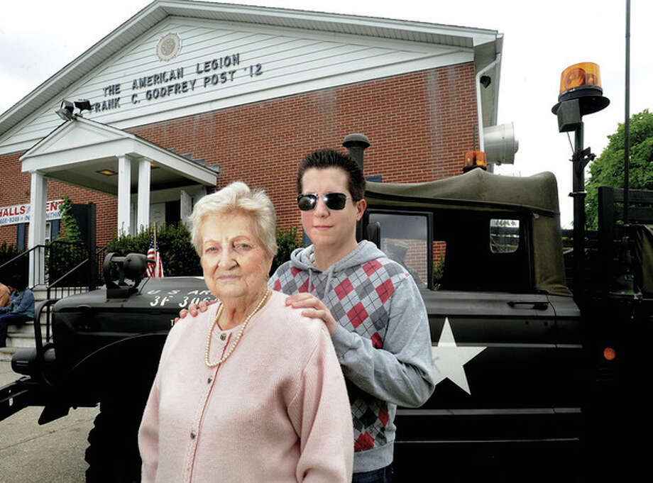 Hour photo / Matthew VinciBeatrice Calzone, wife of Veteran of the Month Nicholas Calzone who served in WWII, stands with her grandson Ryan Mones Sunday at the American Legion Post 12 ceremony.