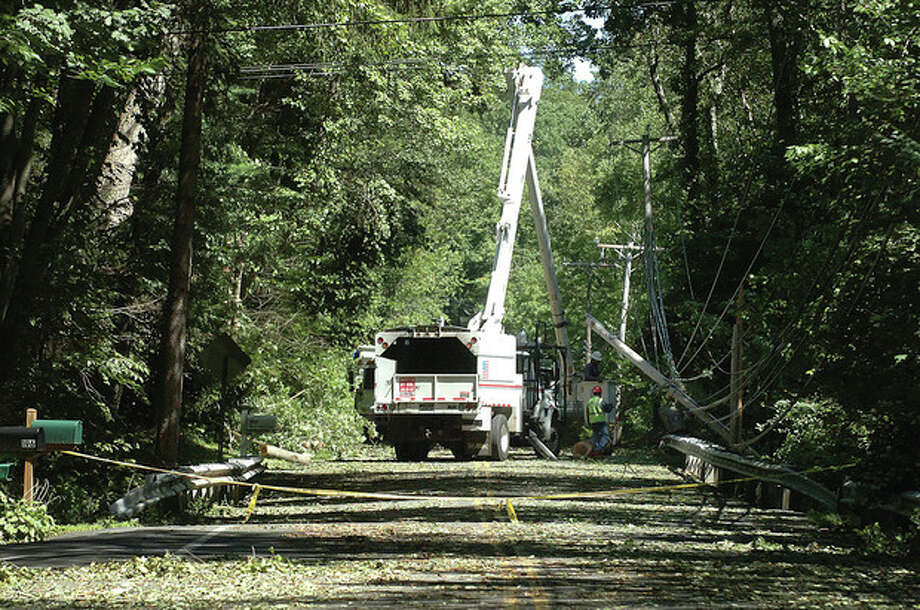 Hour Photo/ Alex von Kleydorff. Utility crews work to restore power along New Canaan Rd in Wilton Monday / 2011 The Hour Newspapers