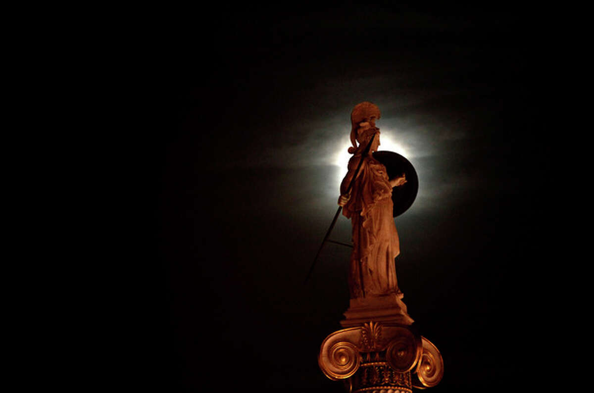 A statue of ancient Greek Goddess Athena is highlighted by the moon, in the center of the Greek capital after elections on Sunday, May 6, 2012. Voters in crisis-hit Greece punished parties that have dominated politics for decades, with parties opposed to the country's bailout agreements gaining ground. (AP Photo/Kostas Tsironis)