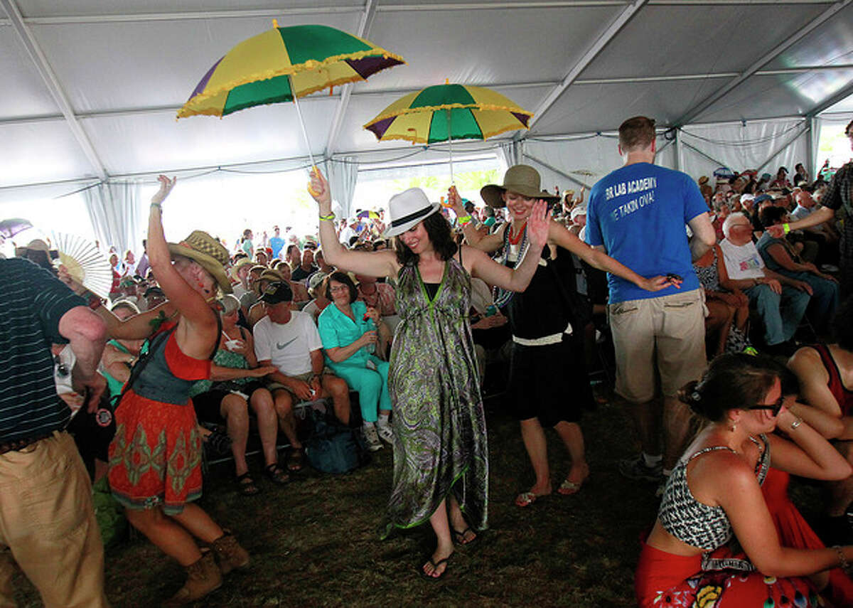 Audience members dance in a second-line as the Preservation Hall Jazz Band performs inside the Economy Tent at the New Orleans Jazz and Heritage Festival in New Orleans, Saturday, May 5, 2012. (AP Photo/Gerald Herbert)