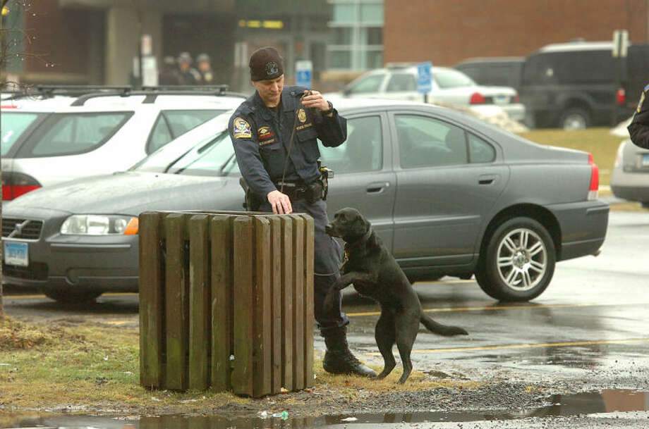 Hour Photo/ Alex von Kleydorff. Weston Police and State Police search the grounds at Weston High School, here a State Trooper uses a K9 to check trash receptacles in the parking area in front of the school.
