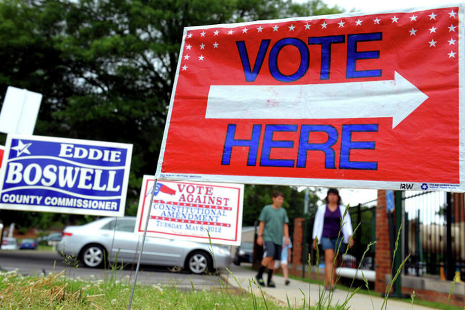 Signs are displayed at the First Presbyterian Church in Burlington, N.C., on Tuesday May 8, 2012, as people approach the building to cast their ballots. North Carolina could be the next state to pass a constitutional amendment defining marriage as solely between a man and a woman. Voters are casting their ballots Tuesday. (AP Photo/Burlington Times-News, Sam Roberts) / The Times-News