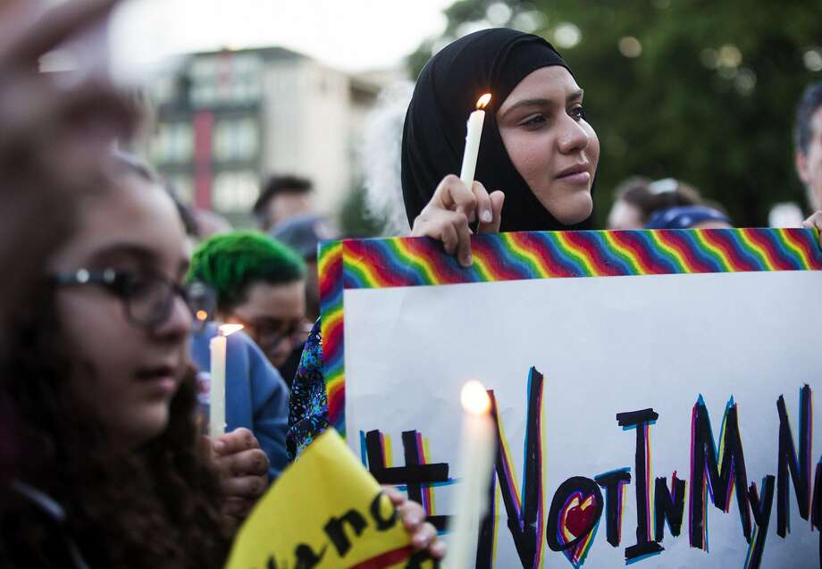"Zuleyha Ozonder, who is Muslim, holds a candle and a sign that references the hashtag ""#NotInMyName"" to show that many in the Islamic faith support the LGBTQ community during a vigil at Cal Anderson Park in Seattle. Photo: Lindsey Wasson, Associated Press"