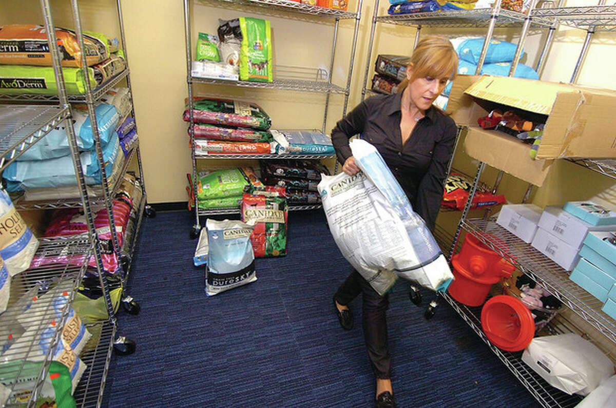 Hour Photo/Alex von Kleydorff. STARrescue Pet food Pantry Executive Director Heather Scutti moves some large bags of dry dog food in the pet food pantry.