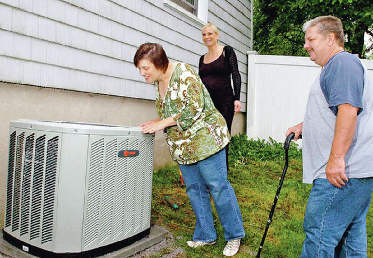 Norwalk residents Kathy and Ed Lane recieve their new central heating and cooling system at their home on West Cedar Wednesday while Gault Director of Sales and Marketing, Megan Smith-Gils looks on. The couple won the system from Gault after entering the Westport company's essay contest,