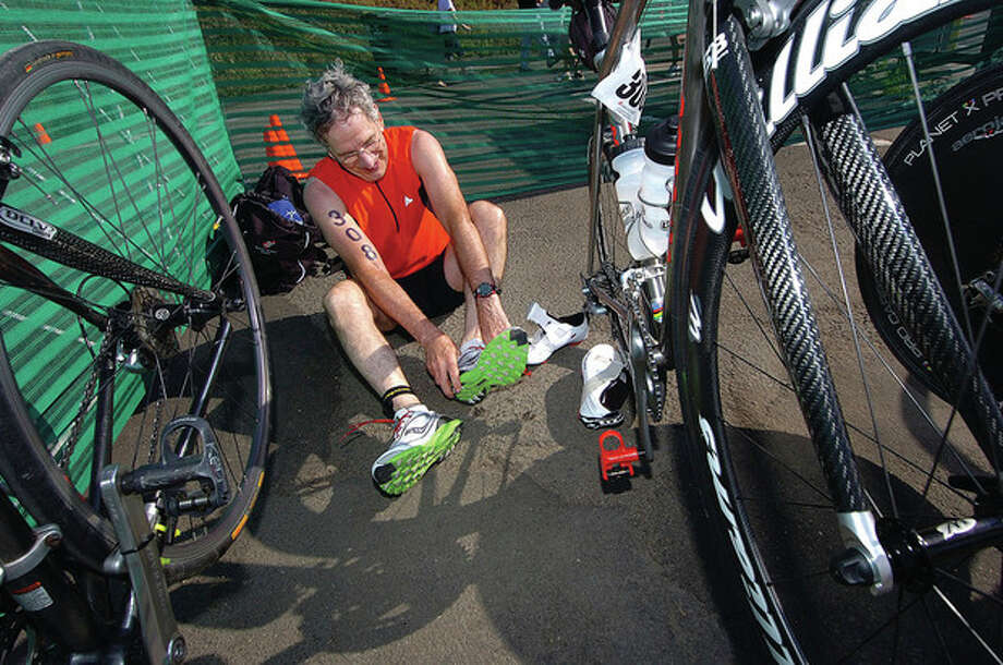 Photo by Alex von Kleydorff. Sanford Friedman leaves his bike and puts on his running shoes at the KIC-IT triathlon in Stamford. / 2011 The Hour Newspapers