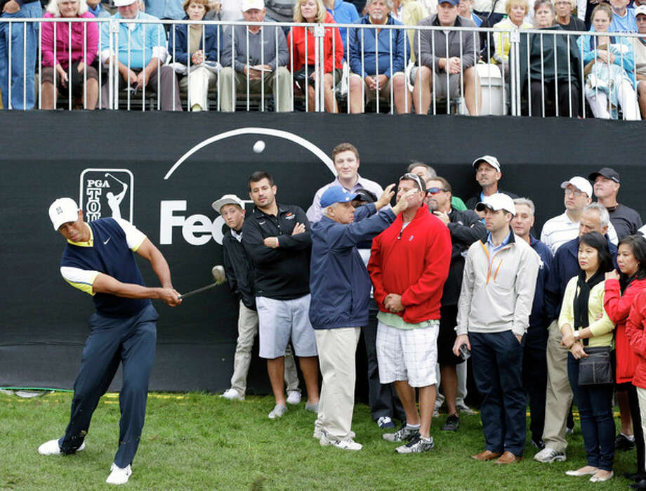 Tiger Woods, left, chips a shot onto the 18th green during the second round of the Honda Classic golf tournament on Friday, March 1, 2013, in Palm Beach Gardens, Fla. (AP Photo/Wilfredo Lee) / AP