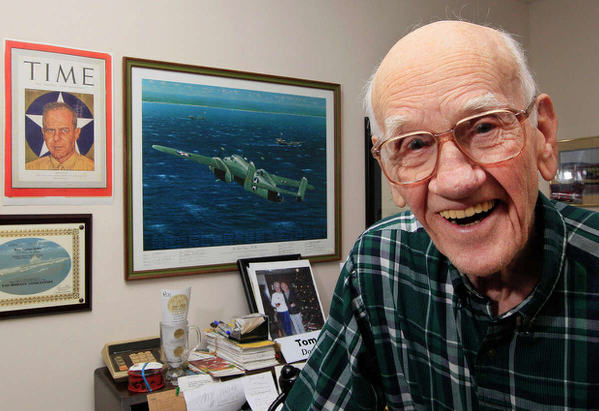 FILE - In this Dec. 1, 2011 file photo, Maj. Thomas Griffin poses for a photo inside his home in Cincinnati, next to a Time Magazine cover of Lt. Col. James Doolittle and a painting of one of the B-25B Mitchell bombers used in Doolittle's raid on Japan in 1942. Griffin, a navigator on one of the planes used in the raid, died Tuesday, Feb. 26, 2013 in a VA nursing home at the age of 96. (AP Photo/Al Behrman, File)