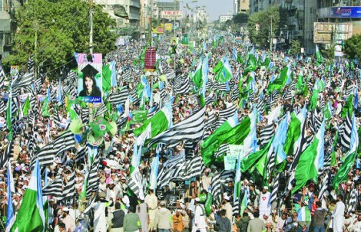 Supporters of Pakistani religious parties wave flags during a rally to protest against any attempts to modify blasphemy laws, in Karachi, Pakistan, Sunday, Jan. 9, 2011.Tens of thousands of demonstrators have marched in Pakistan''s largest city in opposition to any change to blasphemy laws and to praise the man charged with murdering the provincial governor who opposed the legislation.(AP Photo/Fareed Khan)