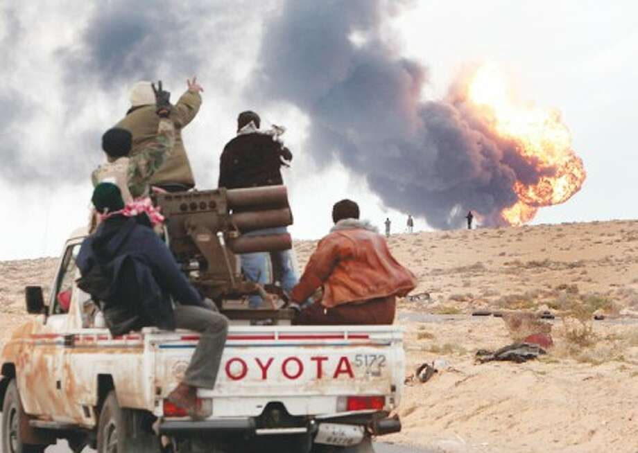 Anti-Gadhafi rebels ride on a truck with a multiple rocket launcher, as flames rises from a fuel storage facility that was attacked during fighting with pro-fighters, in Sedra, eastern Libya, Wednesday March 9, 2011. A high-ranking member of the Libyan military flew to Cairo on Wednesday with a message for Egyptian army officials from Moammar Gadhafi, whose troops pounded opposition forces with artillery barrages and gunfire in at least two major cities. Gadhafi appeared to be keeping up the momentum he has seized in recent days in his fight against rebels trying to move on the capital, Tripoli, from territory they hold in eastern Libya. (AP Photo/Hussein Malla)
