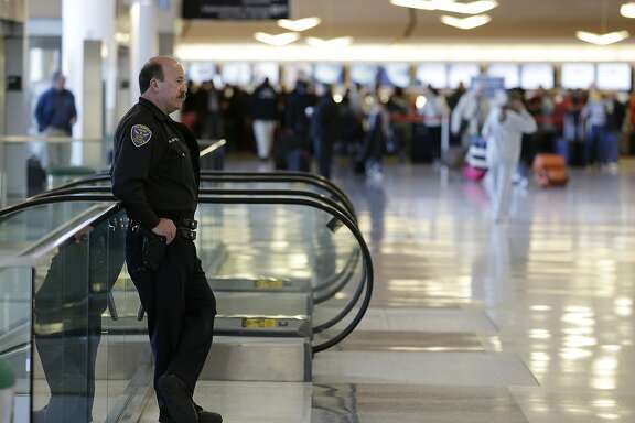 A San Francisco police officer watches over people checking in at terminal two at San Francisco International Airport Tuesday, April 16, 2013 in San Francisco. The airport had an increased security presence following Monday's explosions at the Boston Marathon. (AP Photo/Eric Risberg)