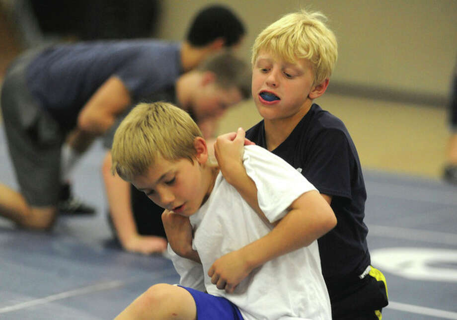 Hour photo/Matthew Vinci Nine-year-olds Will Maggio and Tate Falta practice some of their wrestling moves Tuesday during the Wilton Youth Wrestling camp conducted in the high schoolÕs Zeoli Fieldhouse.
