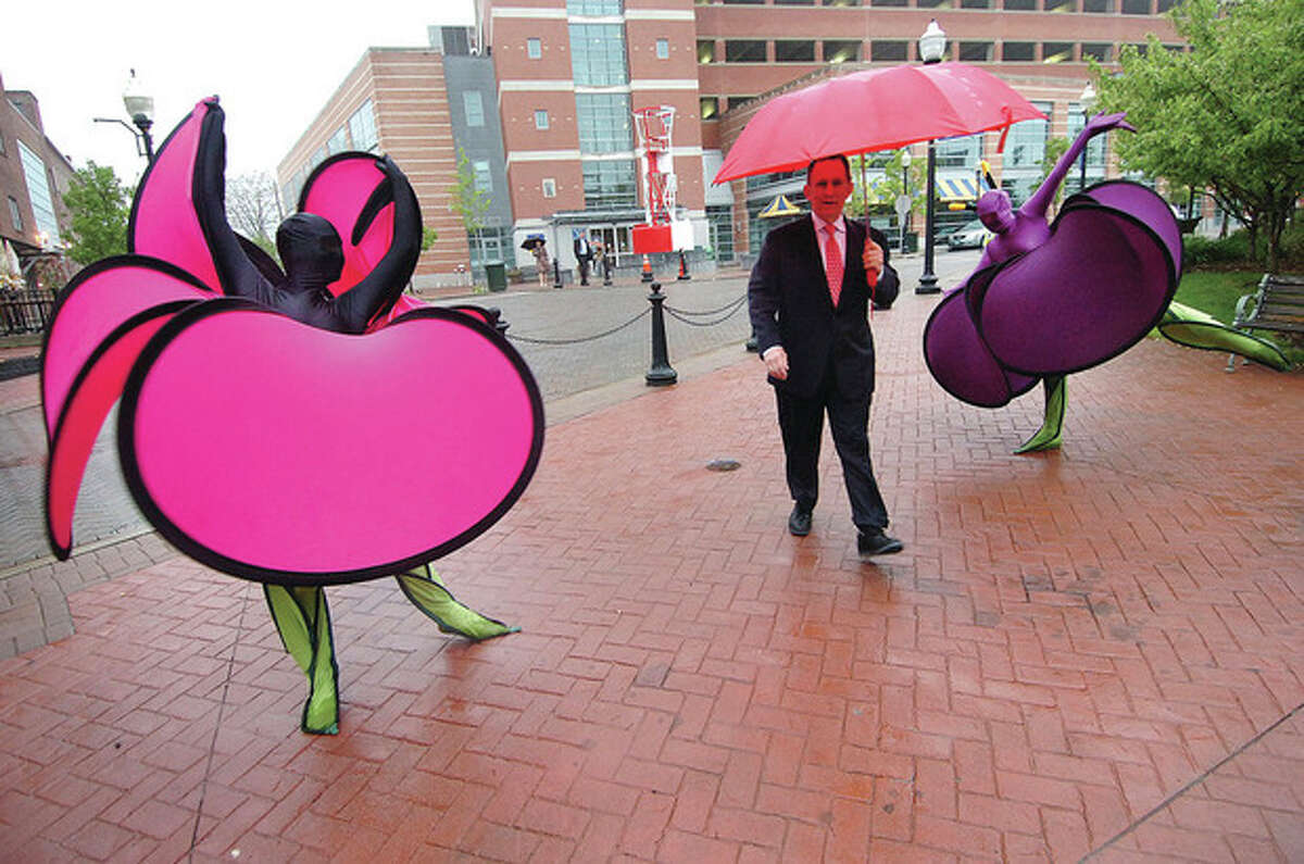 Hour Photo/ Alex von Kleydorff. Fernand Brunschwig with umbrella enters trough human blooming flowers in the rain at the 2012 Red Apple Awards gala at the Maritime Aquarium